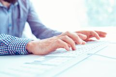 Male hands typing on the keyboard. Male hands or man office worker typing on the keyboard Royalty Free Stock Photography