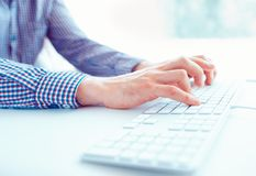 Male hands typing on the keyboard. Male hands or man office worker typing on the keyboard Stock Photography