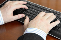 Male Hands Typing on Keyboard. In the Office Stock Photography