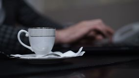 Male hands typing on a laptop. During a coffee break stock video