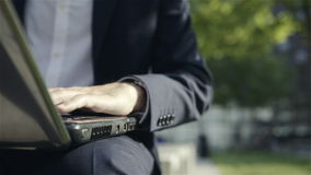 Male hands typing on a laptop keyboard, outdoor stock footage