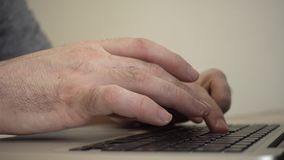Male hands typing on a laptop keyboard. Side view stock footage