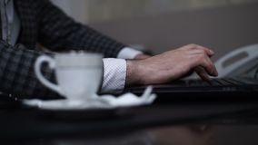 Male hands typing on a laptop. During a coffee break stock footage