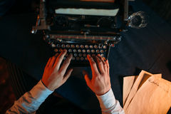 Male hands typing on retro typewriter. Top view. Dark blue table cloth on background. Writer, journalist, literature author, blogger or poet concept Stock Photo