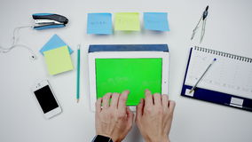 Male hands typing tablet with greenscreen. A man types on a tablet.man working with tablet with green screen at the desk stock footage