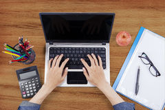Male hands use laptop on wooden desk Stock Photography
