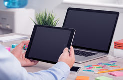 Male hands using ipad digital tablet pc and macbook laptop on the office desk. Businessman holding and working with ipad digital tablet pc. Modern office desk Royalty Free Stock Photos