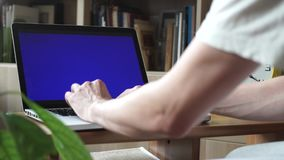Male hands using laptop with green screen in living room. Bookshelves at background stock video footage