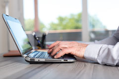 Male hands using a laptop Stock Photography
