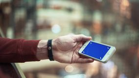 Male hands using smartphone with blue screen in shopping mall. Male hands using smartphone with blue screen in bright shopping mall. Fitness tracker on wrist stock footage