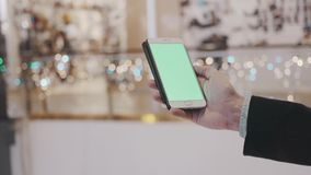 Male hands using smartphone with green screen in shopping mall. Holiday decorations at background. Male hands using smartphone with green screen in shopping mall stock footage