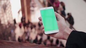 Male hands using smartphone with green screen in shopping mall. Lot of people at the background. HD stock footage