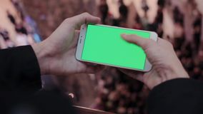 Male hands using smartphone with green screen in shopping mall. Lot of people at the background. HD stock video