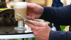 Male hands using smartphone and having cappuccino at cafe in shopping mall. Close-up of man browsing information and. Scrolling pictures on smart phone stock video