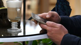 Male hands using smartphone and having cappuccino at cafe in shopping mall. Close-up of man browsing information and. Scrolling pictures on smart phone close up Stock Photos