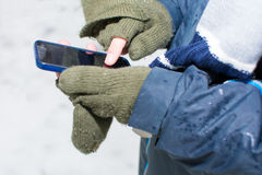Male hands using a smartphone in winter Royalty Free Stock Image