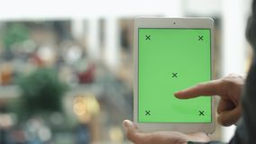 Male hands using tablet with green screen in shopping mall stock video