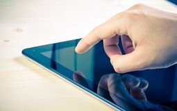 Male hands using tablet pc on wood table. With space for text Royalty Free Stock Images