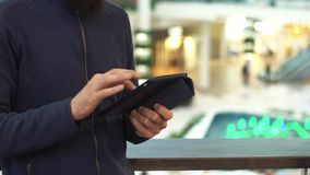 Male hands using tablet in shopping mall.  stock video