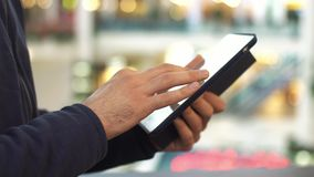 Male hands using tablet in shopping mall.  stock footage