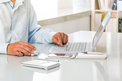 Male hands using touchpad on a laptop at Office. Closeup of a male hands using touchpad on a laptop at Office Royalty Free Stock Image