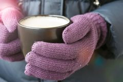 Male hands in violet gloves holding a cup with hot drink royalty free stock images