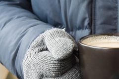 Male hands in violet gloves holding a cup with hot drink royalty free stock photography