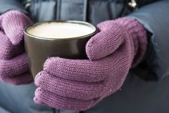 Male hands in violet gloves holding a cup with hot drink royalty free stock photos