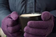 Male hands in violet gloves holding a cup with hot drink stock images