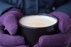 Male hands in violet gloves holding a cup with hot drink stock photo
