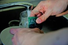 Male hands washing a glass with the help of a sponge.  Royalty Free Stock Photo