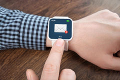 Male hands with white smart watch with email the screen. Male hands with white smartwatch with email on the screen over a wooden table in an office Royalty Free Stock Images