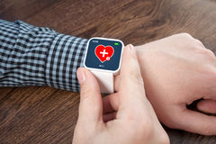Male hands with white smartwatch with mobile app health sensor o Stock Images