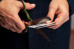 Male hands wirh scissors cutting bank credit card. Closeup of senior male hands wirh scissors cutting bank credit card Royalty Free Stock Photo