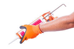Male hands work gloves hold sealant gun Stock Image
