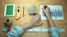 Male hands working with printed graphs making notes with marker at wooden desk. Metal ruler, house model, realistic mockup wooden photo frame, yellow paper stock video footage