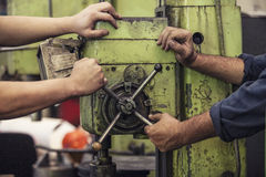 Male hands working twist the lever on the machine in an old fact Royalty Free Stock Image