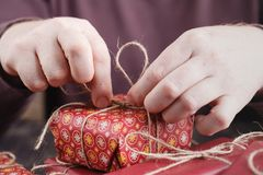 Male hands wrap Christmas gift on wooden table. Stock Images