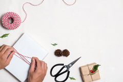 Male hands wrapping xmas gifts. Packages wrapped in kraft paper. Tied with jute Royalty Free Stock Photos