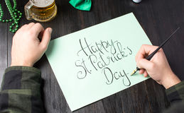 Male hands writing a Happy St Patrick day card. Male hands writing a Happy St Patrick day calligraphy card Stock Photos