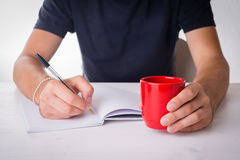 Male hands writing with a  mug and books. Student writing on a blank notebook with a  mug and books Royalty Free Stock Photography