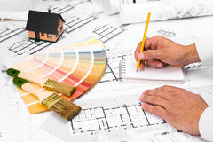 Male Hands writing on notebook. Construction plans with Color Palette and Miniature House on blueprints; Business and Construction Industry Concept Stock Photography