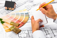 Male Hands writing on notebook. Construction plans with Color Palette and Miniature House on blueprints; Business and Construction Industry Concept Stock Images