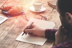 Male hands writing on notebook sitting at coffee shop. Male hands writing on notebook sitting at a wooden table at coffee shop Royalty Free Stock Photos