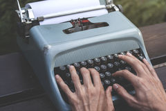 Male hands writing with an old blue typewriter. Vintage stock photo Stock Photo