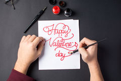Male hands writing a Valentine`s day card. Calligraphy Royalty Free Stock Photography