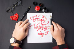 Male hands writing a Valentine`s day card. Calligraphy Royalty Free Stock Photo