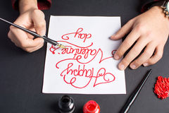 Male hands writing a Valentines day card. Calligraphy Stock Image