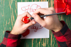 Male hands writing a Valentines day card. Male hands writing a calligraphy Valentines day card Royalty Free Stock Photography