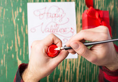 Male hands writing a Valentines day card. Male hands writing a calligraphy Valentines day card Stock Photos